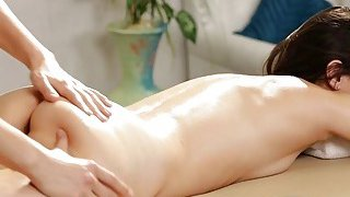Blond masseuse licking with her client on massage table